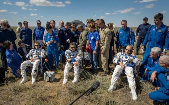 工作人員將太空人扶出聯盟號返回艙後合照