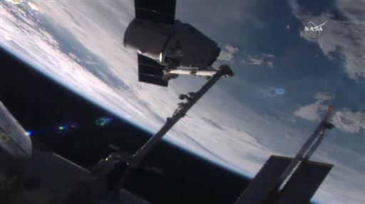 國際太空站上的太空人用機械臂抓住飛龍號太空船