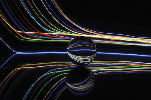 圍繞一塊大理石黑色背景邊緣的光形成的彩色線條
